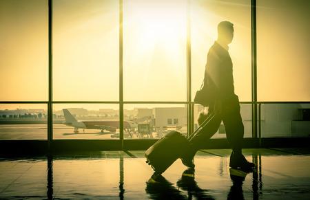 旅行スーツケース ターミナル ゲートへの移動と国際空港でのビジネスの男性