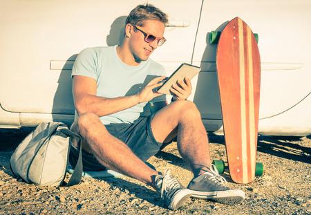 技术: 年輕時髦的男子與平板電腦坐在旁邊他的車 - 復古過濾一下 - 現代科技與復古的生活方式混合概念