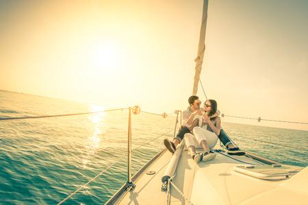Joven pareja de enamorados en el barco de vela con champán al atardecer - Feliz exclusivo concepto lifestye alternativa - Foco suave debido al contraluz en el filtro nostálgico vendimia - lente de ojo de pez y el horizonte inclinado