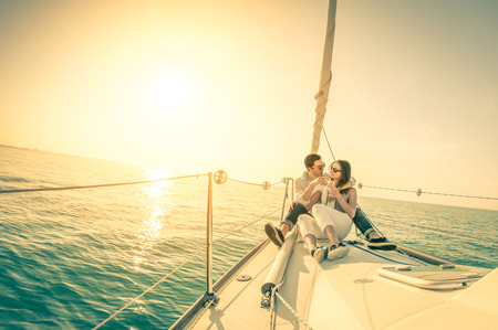 lifestyle: Joven pareja de enamorados en el barco de vela con champán al atardecer - Feliz exclusivo concepto lifestye alternativa - Foco suave debido al contraluz en el filtro nostálgico vendimia - lente de ojo de pez y el horizonte inclinado