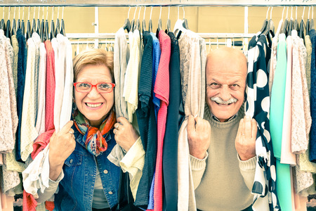 Playful senior couple at weakly flea market - Concept of active elderly with mature man and woman having fun and shopping in the old town - Happy retirement moments on a warm vintage nostalgic look