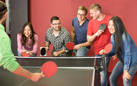 Group of happy young friends playing ping pong table tennis - Fun moment in game room of traveler youth hostel - Concept of vintage sport and genuine emotions - Main focus on two guys with eye glasses Stock Photo