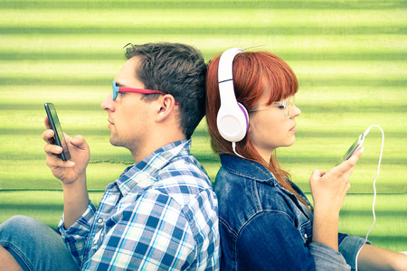 Hipster couple in disinterest moment with mobile phones - Concept of apathy sadness and isolation using new technologies - Boyfriend and girlfriend with smartphones addiction - Vintage filtered look Stock Photo