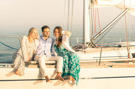 boat party: Young people taking selfie on exclusive luxury sailing boat - Concept of friendship and travel with best friends using modern smartphone as new trends and technology - Warm sunset color tones Stock Photo