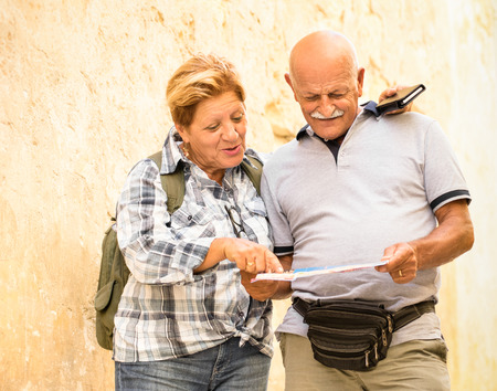 Active senior couple exploring old town of La Valletta with travel map - Concept of youthful elderly and tourist retired lifestyle without age limitation - Warm neutral color tones in cloudy shadow Archivio Fotografico