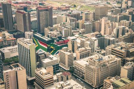 Close up detail of skyscrapers the business district of Johannesburg - Aerial view of modern buildings of the skyline in South Africa biggest city with southafrican flag painted on structure walls Imagens - 39662799