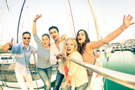 party friends: Best friends using selfie stick taking pic on exclusive luxury sailing boat - Concept of friendship and travel with young people and new technology  trends - Bright nostalgic desaturated color tones Stock Photo