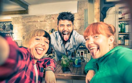 barra de bar: Camarero hermoso joven coqueteando con chicas bellas en bar de c�cteles - Novias felices que toman selfie con camarero fresco en el club de noche - mirada filtrada Vintage y bordes borrosos - Enfoque en la cara masculina Foto de archivo