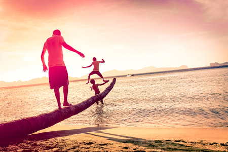Father playing with sons at tropical beach with tilted horizon - Concept of  family union with man and children having fun together - Modified unrecognizable silhouettes - Marsala filtered color tones Stock Photo