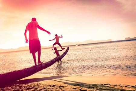 padres: Padre jugando con hijos en la playa tropical con horizonte inclinado - Concepto de uni�n familiar con el hombre y los ni�os se divierten juntos - Modificado siluetas irreconocibles - Marsala filtra tonos de color
