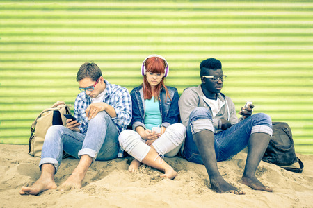Group of young multiracial friends with smartphone and mutual disinterest towards each other - Social situation of new technology interaction in alienated lifestyle - Vintage nostalgic filtered look