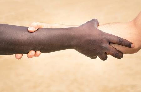 racismo: Manos blancas y negras en el apretón de manos moderna para mostrar el uno al otro la amistad y el respeto - Ayudar y respetando mutuamente contra el racismo - Ligeramente crujiente mirada filtrada detallada sobre el fondo desenfocado Foto de archivo