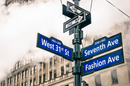 road sign: Modern street sign and vapor steam in New York City - Urban concept and road traffic directions in Manhattan downtown - American world famous capital destination on dramatic desaturated filtered look