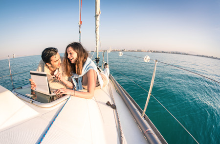 라이프 스타일: 태블릿과 항해 보트 재미에 사랑에 젊은 부부 - 요트 요트에 행복 럭셔리 라이프 스타일 - 위성 무선 랜 연결과 기술의 상호 작용 - 어안 렌즈 왜곡 라운드 수평선