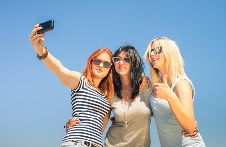 Happy girlfriends taking selfie against blue sky - Friendship summer concept with new trends and technology - Best friends enjoying moments with modern smartphone - Warm sunny afternoon color tones Stock Photo