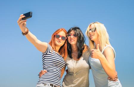 mejores amigas: Novias felices que toman selfie contra el cielo azul - concepto Amistad verano con las nuevas tendencias y la tecnología - Mejores amigos disfrutando de momentos con smartphone moderno - Los colores cálidos tarde soleada Foto de archivo
