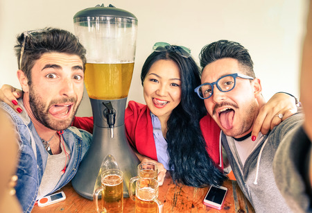 Happy friends taking selfie with funny tongue out near beer tower dispenser - Concept of friendship and fun with new trends and technology -  Alternative everyday party life in vintage brewery bar