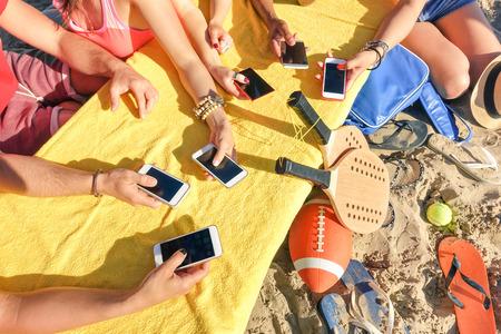 riendo: Grupo de amigos multirraciales que se divierten junto con el teléfono inteligente - Primer plano de las manos mixtos de redes sociales con el teléfono móvil inteligente en día soleado - Concepto de la tecnología en la playa del verano del estilo de vida cotidiana
