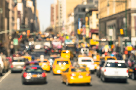 new automobiles: Rush hour with defocused cars and yellow taxi cabs - Traffic jam in Manhattan downtown - Blurred bokeh postcard of New York City with warm sunny day color tones - Real life transportation concept Stock Photo