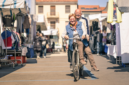 Happy senior couple having fun with bicycle at flea market - Concept of active playful elderly with bike during retirement - Everyday joy lifestyle without age limitation in a spring sunny afternoon Archivio Fotografico