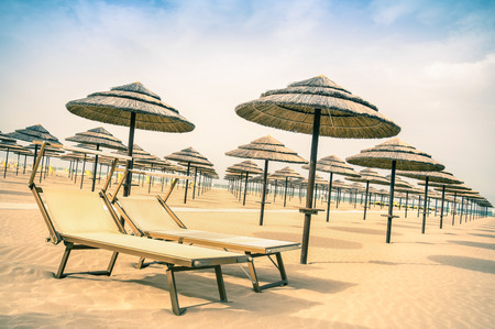 adriatic: Straw umbrellas and sunbeds at Rimini beach in Italy - Top destination in Emilia Romagna adriatic coast - Vintage filtered look of the world famous italian Riviera with tilted horizon composition Stock Photo