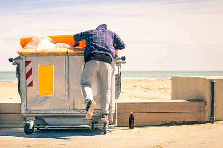 poverty: Young tramp rummaging in trash container looking for food and reusable goods - Modern concept of poverty with normal citizens becoming suddenly poor - Economy crisis and people with living issues