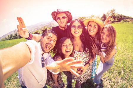 amicizia: Migliori amici prendendo selfie alla campagna picnic - Felice concetto di amicizia e divertimento con i giovani e le nuove tendenze tecnologiche - sguardo filtro vintage con toni di colore marsala - lente fisheye distorsione