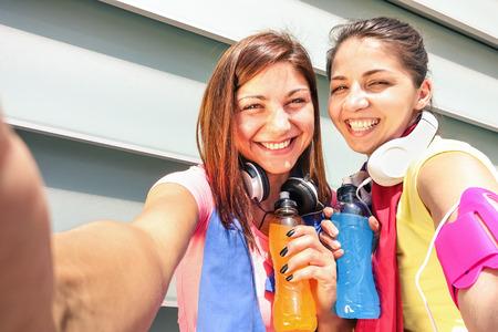 фитнес: Спортивное подруги, принимающие selfie во время перерыва в обучении выполнения в городской местности - Спорт Молодые счастливых женщин веселились вместе с фитнес-тренировки бег - Мода спортивной одежды и энергетические напитки