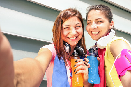 健身: 動感十足的女朋友在運行培訓,市區休息期間採取selfie  - 體育年輕快樂的女性獲得樂趣與健身慢跑鍛煉起來 - 時尚運動服飾和充滿活力的飲料
