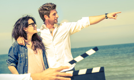 Young couple in love acting for romantic film at beach - Cinema industry concept with ciak slate ready for movie scene - Modern lifestyle with confident guy and happy girlfriend - Focus on male face