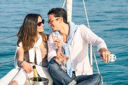 bonne aventure: Jeune couple dans l'amour sur le bateau à voile avec des lunettes de flûte de champagne Bonne exclusive lifestye concept alternatif de copain et copine flirter sur voilier de luxe après-midi ensoleillé tons de couleurs