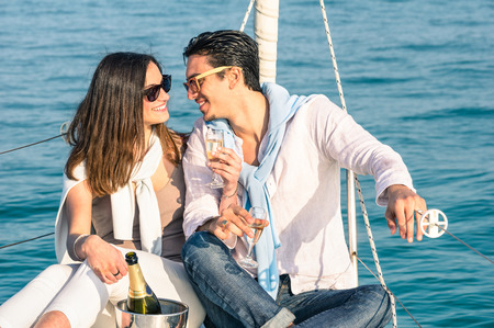 bow of boat: Young couple in love on sail boat with champagne flute glasses  Happy exclusive alternative lifestye concept  Boyfriend and girlfriend flirting on luxury sailboat  Sunny afternoon color tones