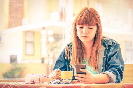 Retrato de la vendimia filtrada de graves mujer joven pensativa con la muchacha del inconformista smartphone mediante teléfono móvil inteligente, mientras que beber café Concepto de las emociones humanas enfoque suave en el rostro preocupado triste