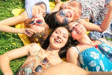 friendship: Copines multiraciales prenant selfie au pique-nique campagne concept de l'amitié heureux et amusant avec les jeunes et les nouvelles tendances de la technologie de Sunny tons de couleur de l'après-midi smartphones tenant Encadrée main Banque d'images