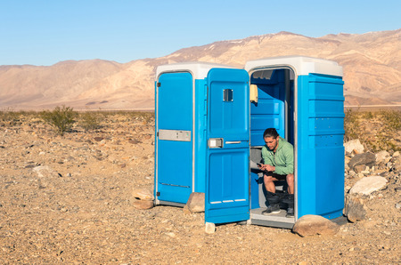 Man sitting in the Toilet in the middle of the desert  Death Valley California