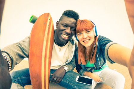 fun: Hipster multiracial couple in love taking selfie on white background  Fun concept with alternative fashion and technology trends  Redhead girlfriend with afro american guy  Vintage filtered look