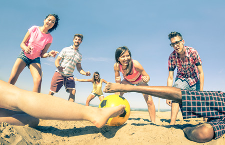 Group of multiracial friends playing beach soccer at beginning of summer  Concept of multi cultural friendship fun and sport against racism  Vintage filter with main focus on girl near the ball Standard-Bild