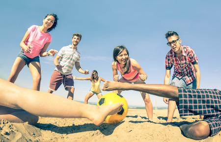 jugando futbol: Grupo de amigos multirraciales jugando al fútbol playa al comienzo del Concepto verano de múltiples diversión amistad cultural y deportiva contra el racismo filtro de la vendimia con el foco principal en la niña cerca de la pelota Foto de archivo
