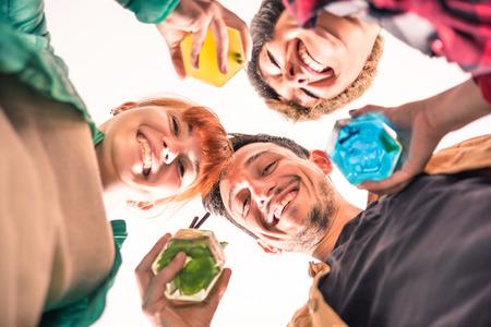 jovenes tomando alcohol: Mejores amigos en un c�rculo sonriendo juntos a la c�mara Felices los j�venes bebiendo c�cteles multicolores concepto de diversi�n y reuni�n social poca profundidad de campo con enfoque en los ojos del individuo Foto de archivo