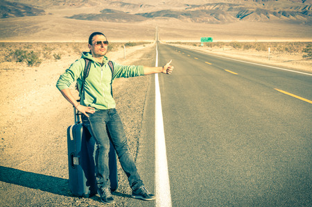 hitch hiker: Young handsome man hitchhiking in the Death Valley  California National Park Stock Photo