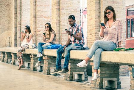 tecnologia: Gruppo di giovani amici multirazziali che utilizzano smartphone con reciproco disinteresse verso l'altra dipendenza Technology di stile di vita attuale soft look vintage filtrata con focus principale sulla persona di sesso maschile