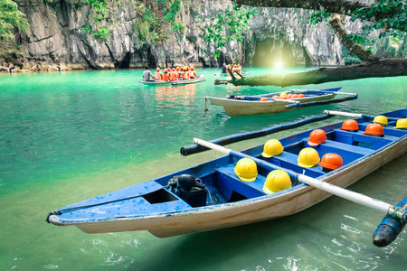 Longtail boats at cave entrance of Puerto Princesa subterranean underground river  Nature trip in Palawan exclusive Philippines destination  People with light equipment during adventurous excursion
