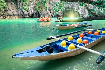 Longtail boten in grot ingang van Puerto Princesa ondergrondse ondergrondse rivier Natuur reis in Palawan Filippijnen exclusieve bestemming Mensen met een lichte apparatuur tijdens avontuurlijke tocht Stockfoto