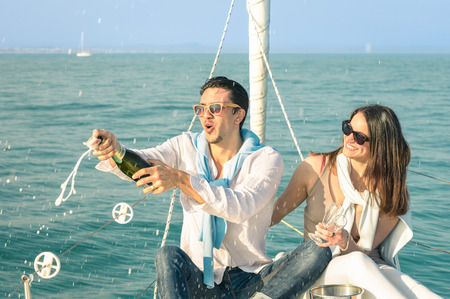Young couple in love on sailing boat cheering with champagne wine bottle - Happy girlfriend birthday party cruise travel on luxury sailboat - Focus on boyfriend face with sunny afternoon color tones Archivio Fotografico