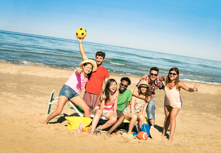 Group of multiracial happy friends having fun with beach sport games  International concept of summer joy and multi ethnic friendship all together   Sunny afternoon color tones with tilted horizon Stock Photo