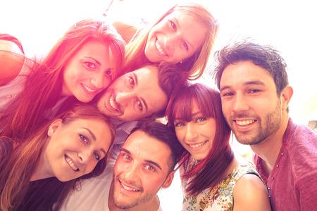 přátelé: Nejlepší přátelé, kteří se selfie venku s podsvícením kontrastní Šťastný přátelství koncept s mladými lidmi, baví se spolu vintage vzhled s filtrovanou marsala barevných odstínech a sluneční svit halo světlice