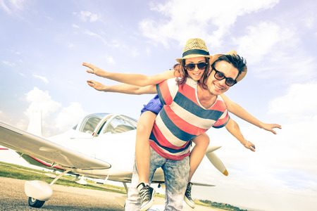 male friends: Happy hipster couple in love on airplane travel honeymoon vacation  Summer concept with male and female models at exclusive trip excursion  Best friends having fun  Bright vintage filtered look Stock Photo