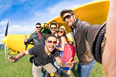Having Fun: Best friends taking selfie at aeroclub with ultra light airplane