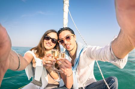 parejas: Joven pareja de enamorados tomar selfie en bote de vela que anima con el vino del champán fiesta jubilar feliz viaje de crucero en velero de lujo con novio y novia tono de color brillante tarde soleada