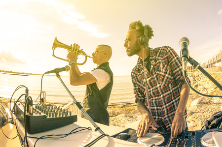 Trendy hipster dj playing summer hits at sunset beach party with trumpet jazz performer  Holidays vacation concept at open air club with house music groove location  Warm vintage sunshine filter